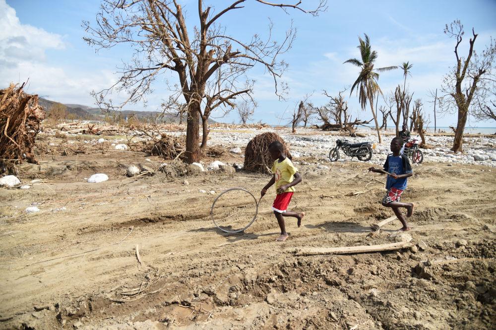 Děti ženou kolo v Les Cayes na Haiti, kam udeřil hurikán Matthew