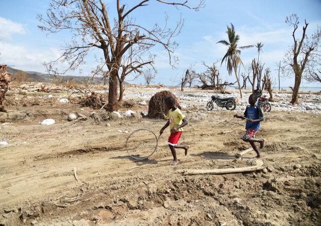 Děti ženou kolo v Les Cayes na Haiti, kam udeřil hurikán Matthew. Ilustrační foto