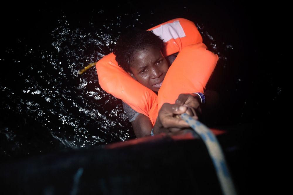 Holčička se drží za lano během operace na záchranu tonoucích uprchlíků u břehů Libye