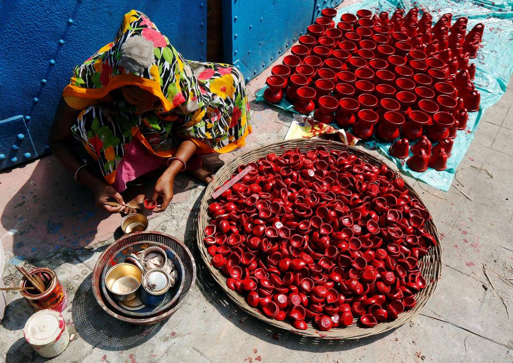 Žena maluje keramické lampy v indické Kalkatě