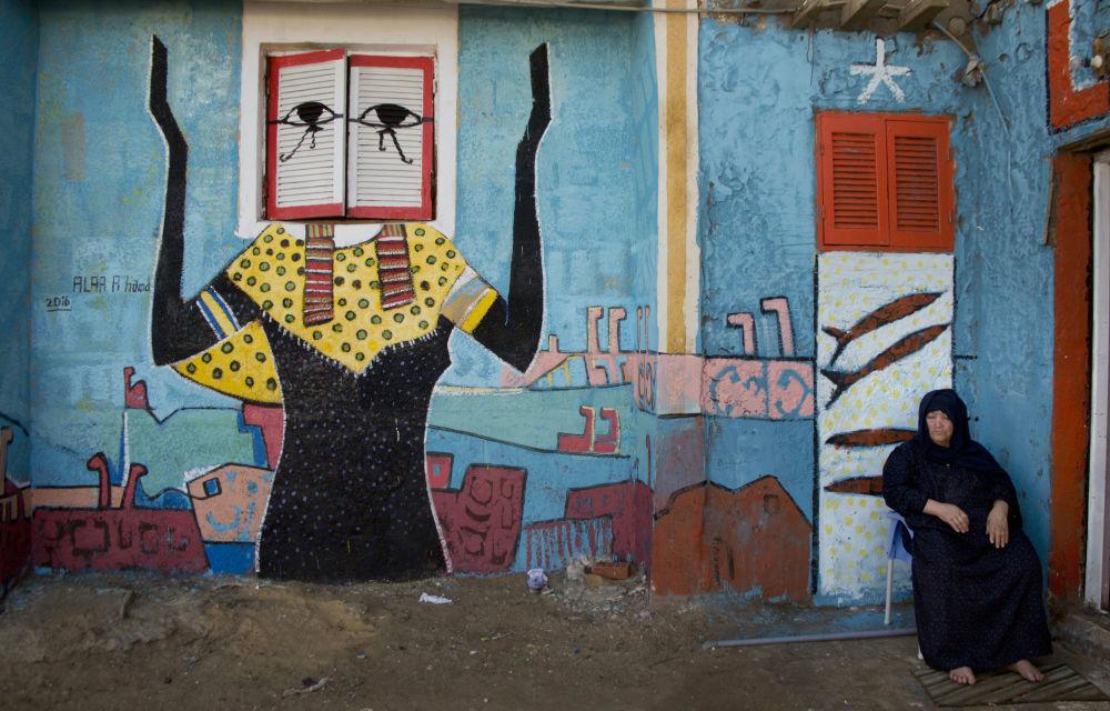 Žena s freskou egyptského malíře Alé Abula Hamada v pozadí v městě Burullus
