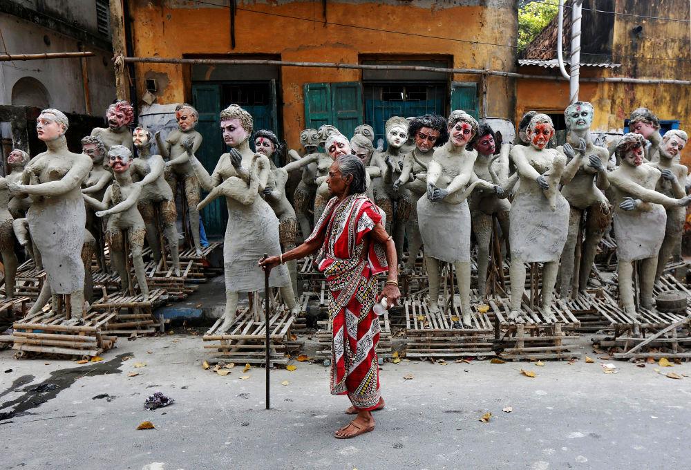 Žena vedle nedokončených hliněných soch hinduistických postav, jež mají být postaveny kolem bohyně Kálí na festivalu Kálí-pudža v Kalkatě