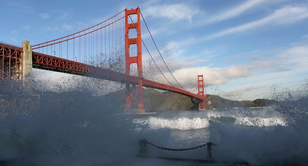 Waves crash against a sea wall in San Francisco Bay beneath the Golden Gate Bridge in San Francisco