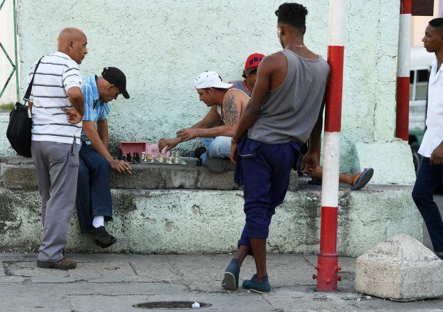 Muži hrají šachy v historické části Havany