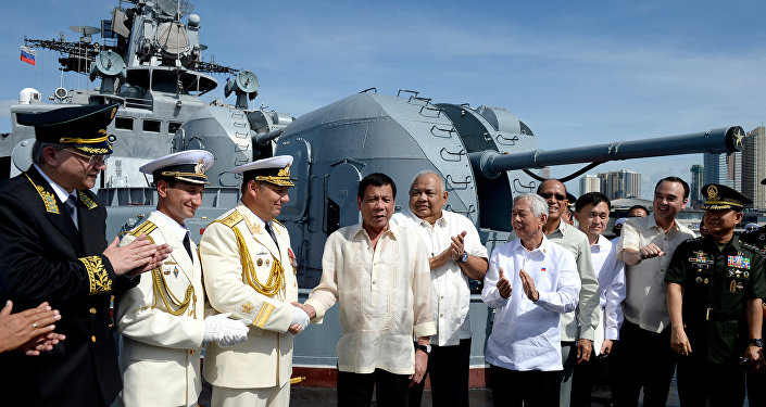 Philippine President Rodrigo Duterte (4th L) shakes hands with Russia's Rear Admiral Eduard Mikhailov at the anti-submarine navy ship Admiral Tributs at the south pier in Metro Manila, Philippines January 6, 2017