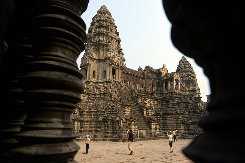 Tourists take photos of the Angkor Wat temple in Siem Reap province on March 20, 2015