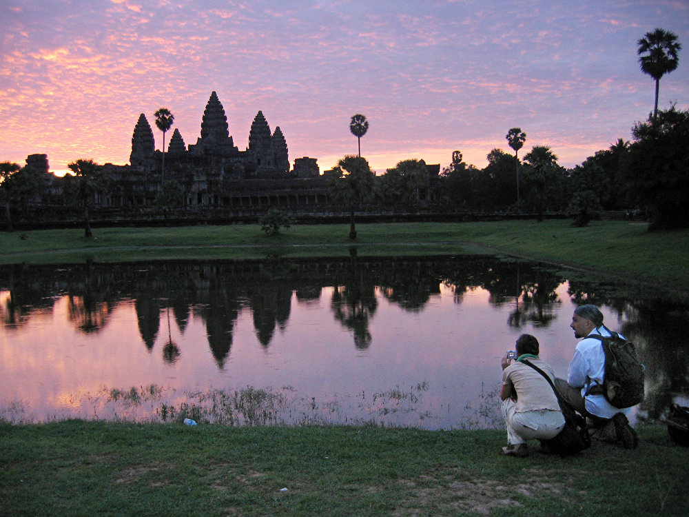 In this July 14, 2014 file photo, tourists look at the view of the Angkor Wat temples at sunrise, outside Siem Reap, Cambodia