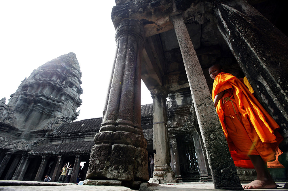 In this photo taken Friday, July 16, 2010, a monk strolls through Angkor Wat in Siem Reap province, about 143 miles (230 kilometers) northwest of Phnom Penh, Cambodia