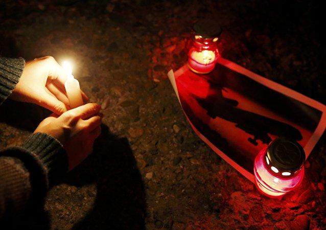 Lidé přinášejí svíčky, aby uctili památku obětí havárie Tu-154