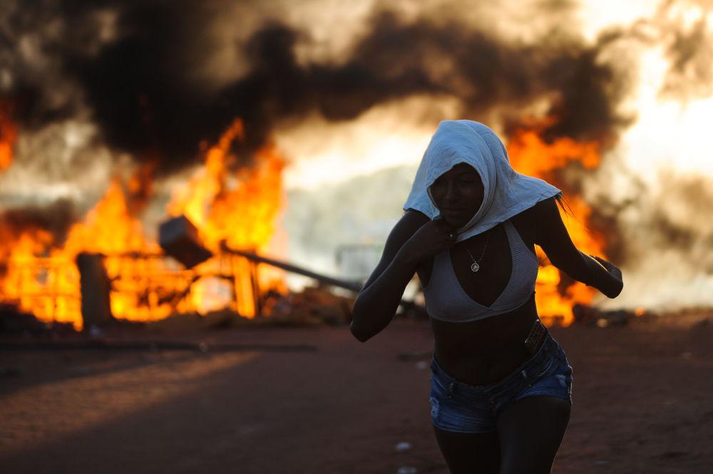 Běžící dívka s ohněm v pozadí během protestů v Brazílii