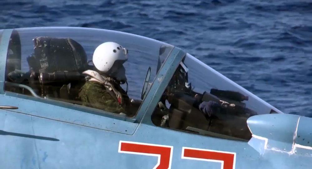 Letec na stíhačce Su-33 na palubě křižníku Admirál Kuzněcov
