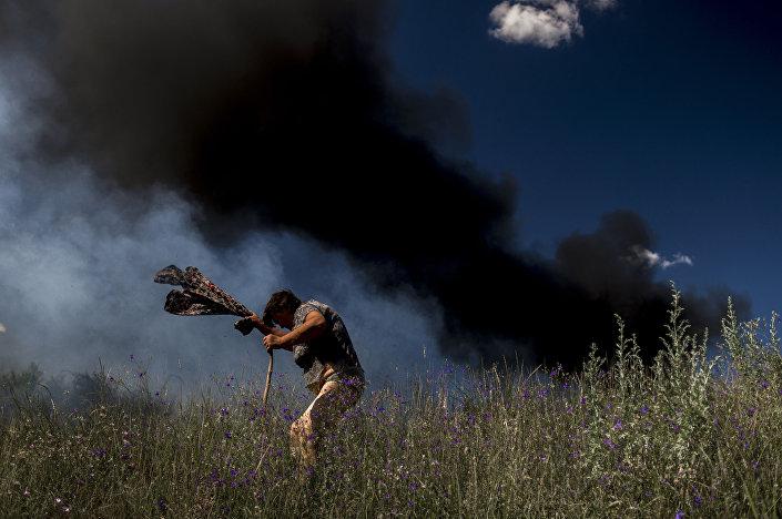 Obyvatelka Luhansku vedle auta, které začalo hořet v důsledku zásahu střely během ostřelování ukrajinskými vojáky
