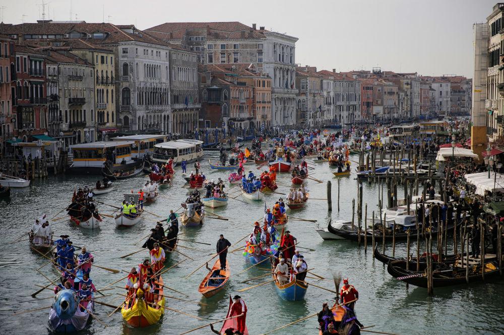 Účastníci maškarní přehlídky plují kanálem Grande během Benátského karnevalu