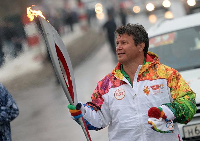 Ruský a americký herec a sportovec Oleg Taktarov nese olympijský oheň