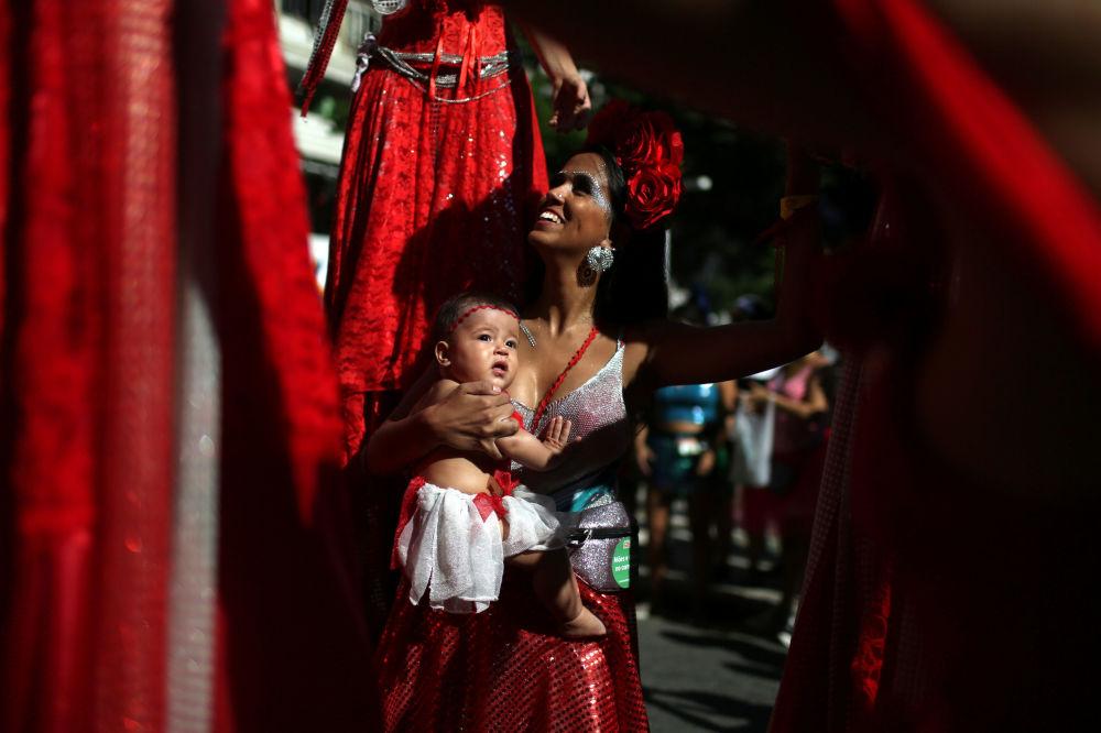 Dívka s dítětem v náručí během zábavy před karnevalem v Riu de Janeiru
