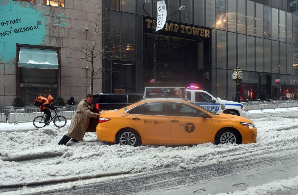 Cestující tlačí taxík uvízlý v sněhu po bouřce Stella v New Yorku