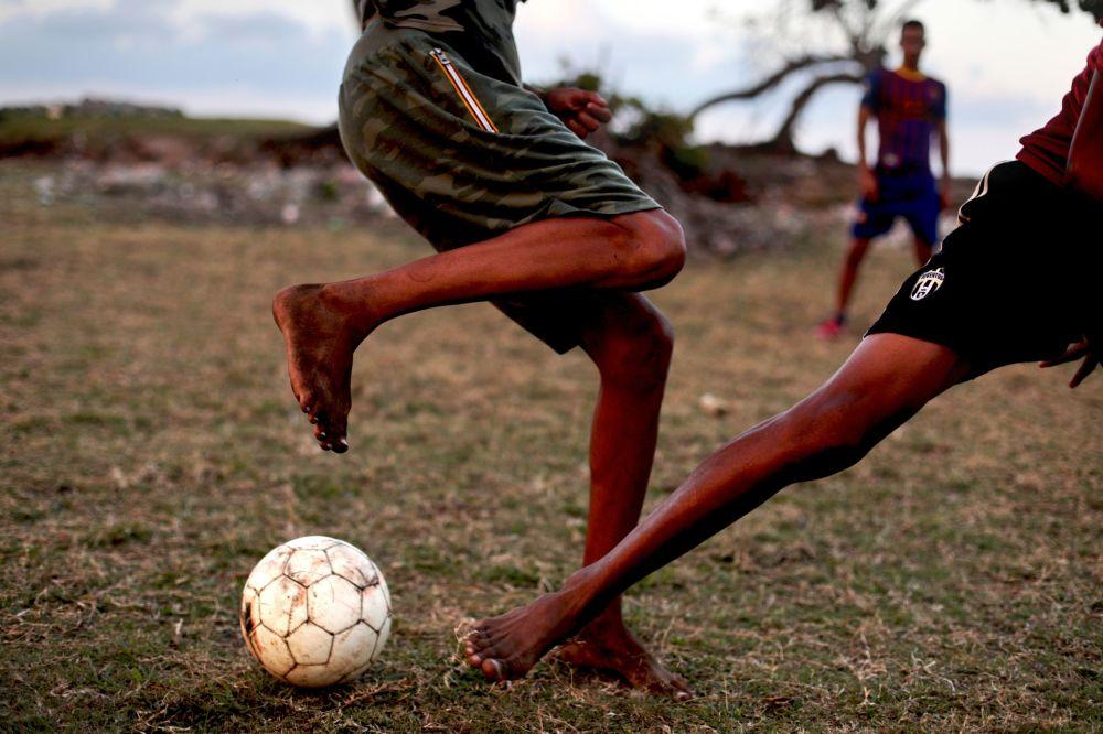 Kubánci hrají fotbal na baseballovém hřišti v městě Baracoa
