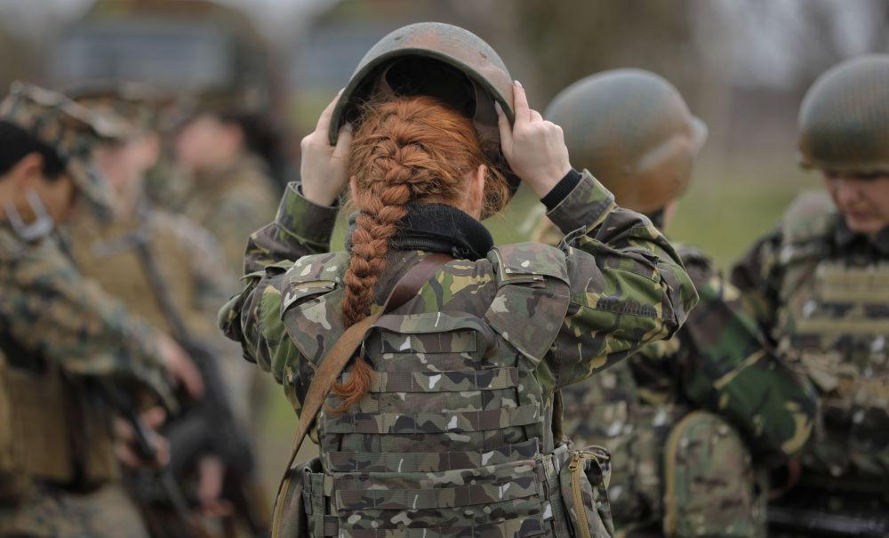 Rumunská vojenská příslušnice si upravuje přilbu na cvičení spolu s americkými vojačkami na rumunském pobřeží Černého moře