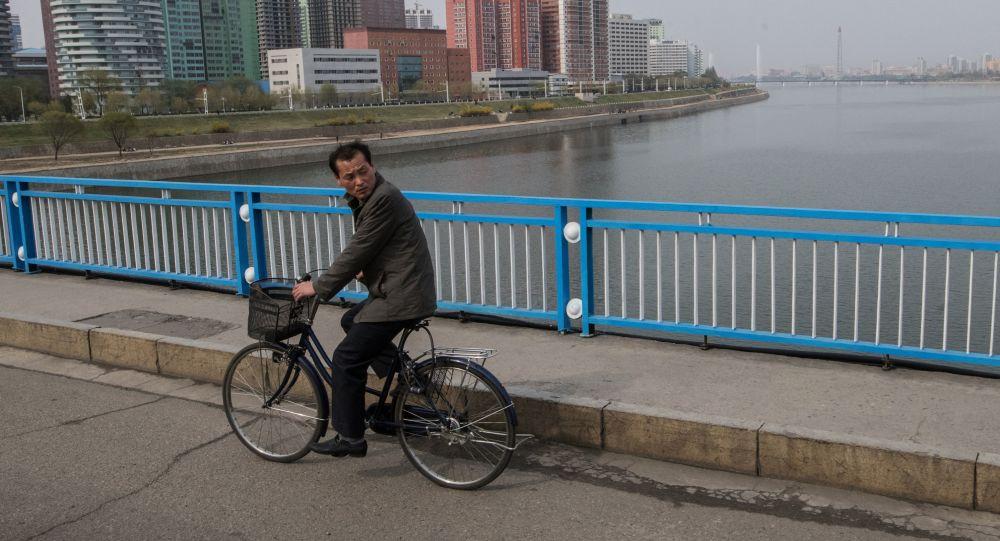 Muž jede na kole v Pchjongjangu