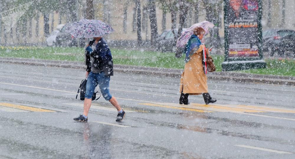 Chodci přecházejí ulici v Moskvě během sněžení