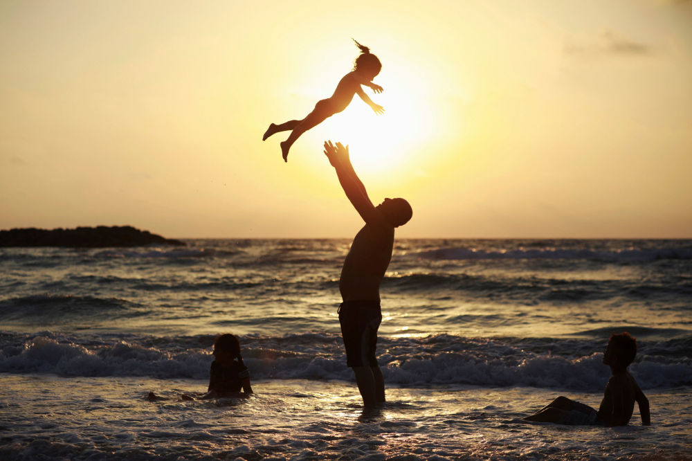 Muž si hraje s dcerou na pláži během oslav Uraza bajramu v Aškelonu, Izrael