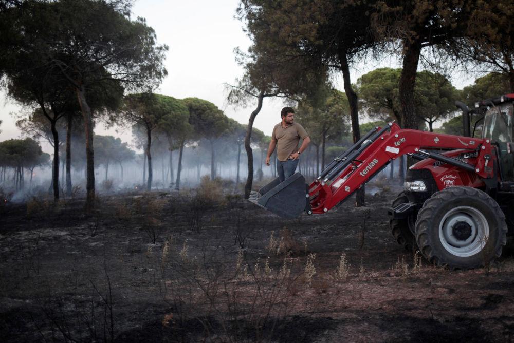Muž na traktoru pomáhá hasit lesní požár na jihu Španělska