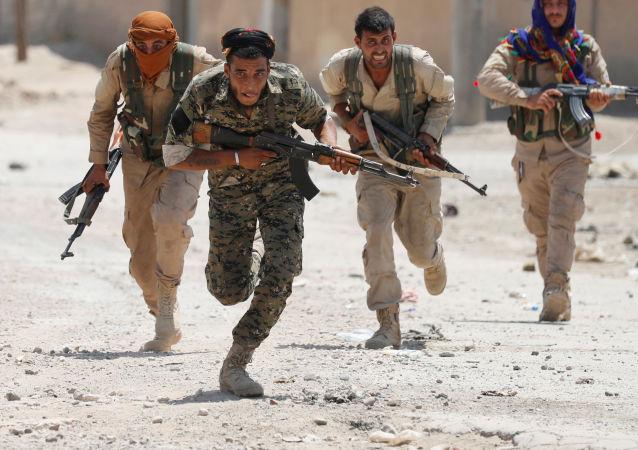 Kurdští bojovníci z Oddílu národní sebeobrany běží po městě Rakka, Sýrie