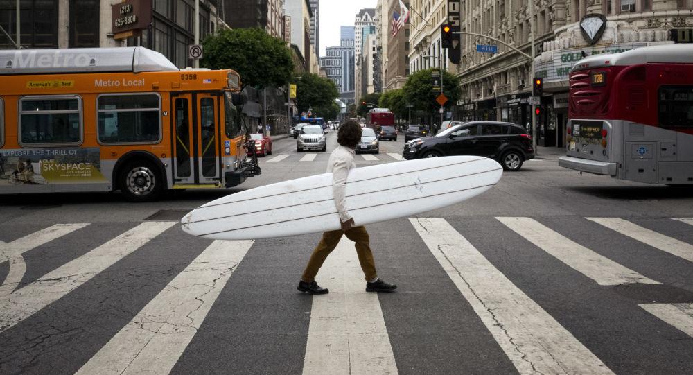 Muž se surfingovým prknem na ulici v Los Angeles, USA