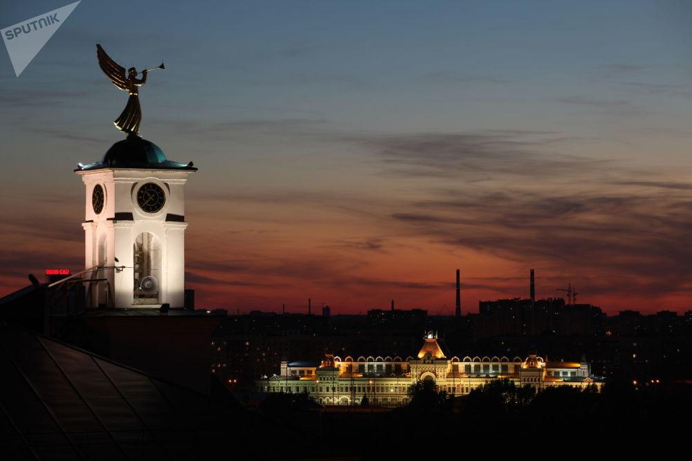 Hodinová věž nižněnovgorodského semináře s korouhvičkou ve tvaru anděla a Nižněnovgorodský jarmark v Nižním Novgorodu