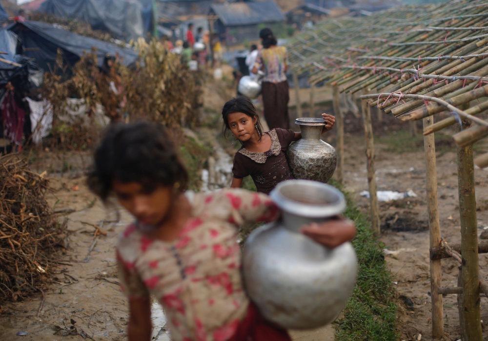 Děvčátka z rodin běženců Rohindža nesou džbány s vodou, Bangladéš