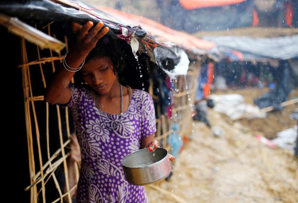 Dívka patřící k běžencům z etnika Rohingyů sbírá dešťovou vodu v přechodném táboře ve městě Cox's Bazar v Bangladéši