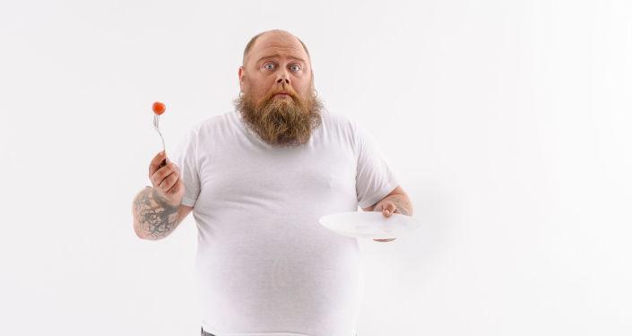 Muž s talířem a vidličkou