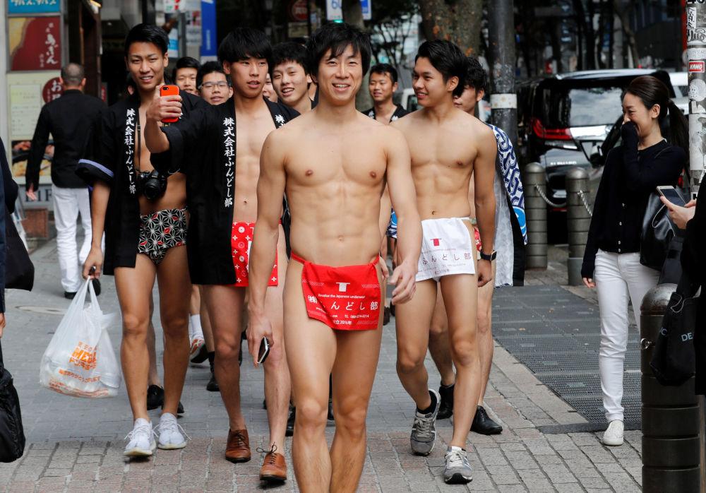 Japonci v tradičním spodním prádle fundoši během akce sběru odpadu na ulicích japonského Tokia