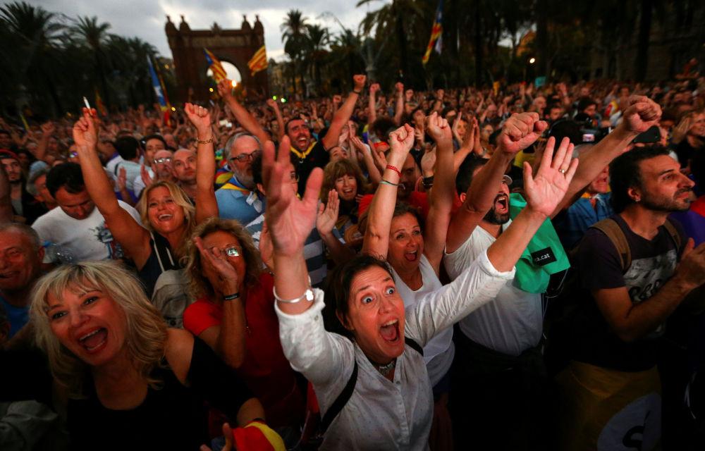 Lidé se dívají na přenos zasedání Katalánského regionálního parlamentu během mítinku za nezávislost v Barceloně