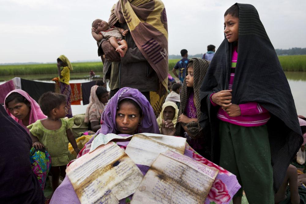 Žena Rohindža na útěku z Barmy do Bangladéše suší své doklady na hranici