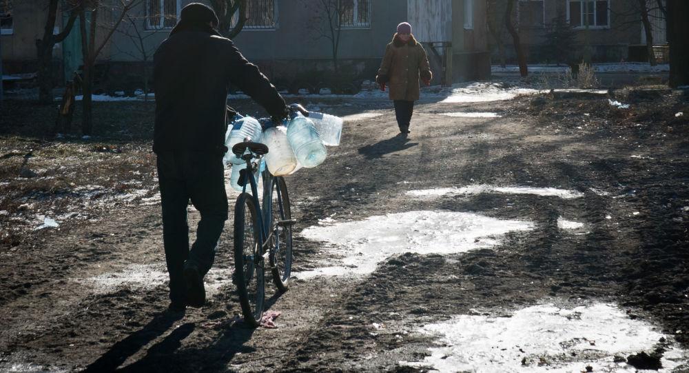 Muž jde pro pitnou vodu v městě Debalceve
