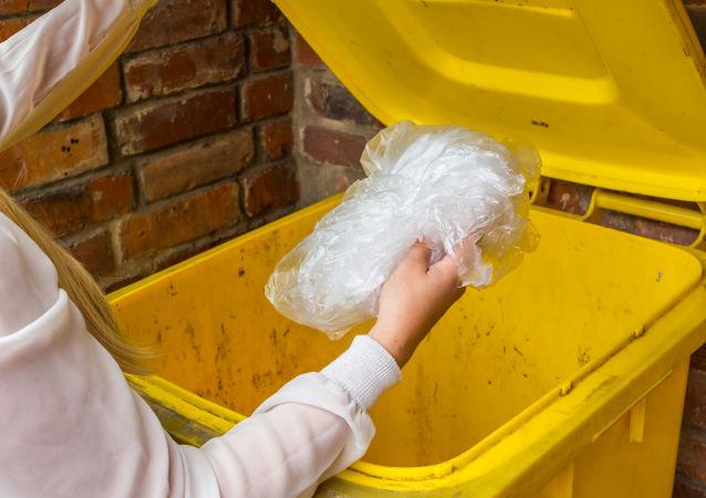 Žena vyhazuje pytel do odpadkového koše