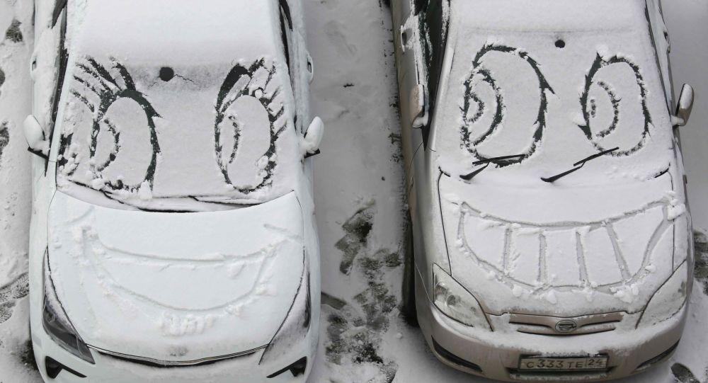 Ksichtíky na zasněžených čelních sklech aut v Krasnojarsku