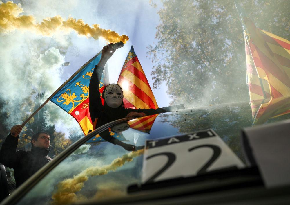 Maskovaný muž s dýmovnicí během stávky taxikářů v Madridu