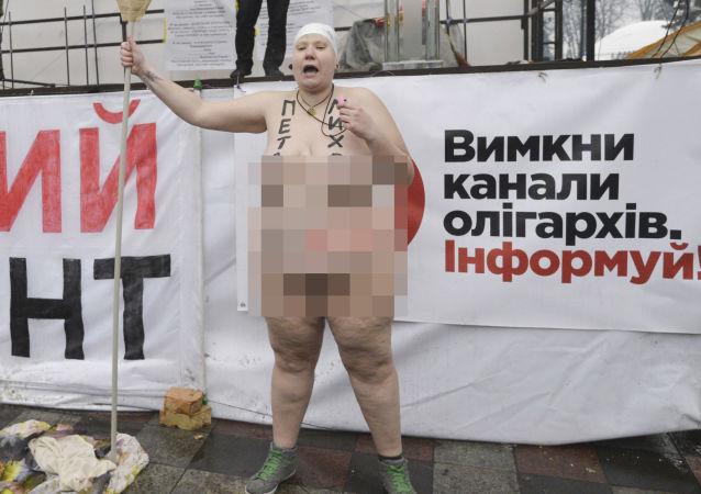 Nahá obyvatelka Kyjeva s veslem v ruce
