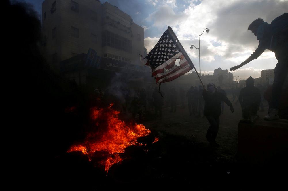 Palestinci spalují americkou vlajku během srážek s izraelskou policií kvůli protestům proti rozhodnutí Donalda Trumpa o uznání Jeruzalému za hlavní město Izraele