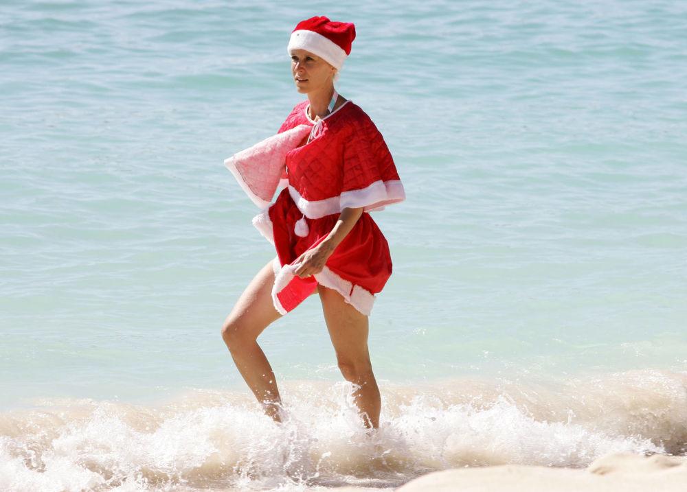 Žena v kostýmu Santa Klause na pláži Guadeloupe