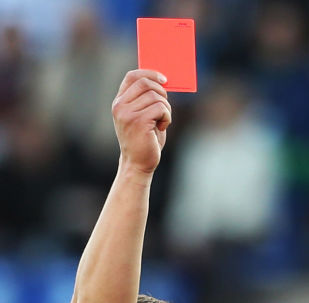 Fotbalový rozhodčí během zápasu ukazuje červenou kartu. Ilustrační foto