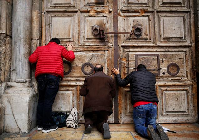 Lidé se modlí u zavřených dveří do Chrámu Božího hrobu v Jeruzalémě