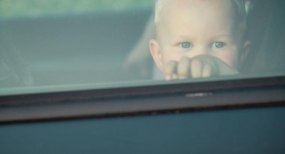 Malé dítě se dívá přes okno automobilu