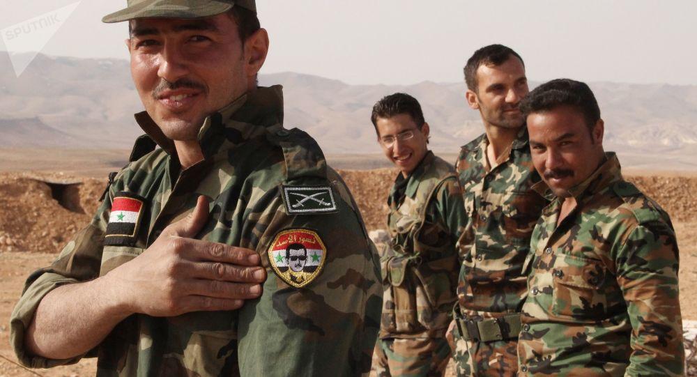 Syrský voják ukazuje na portrét Bašára Asada