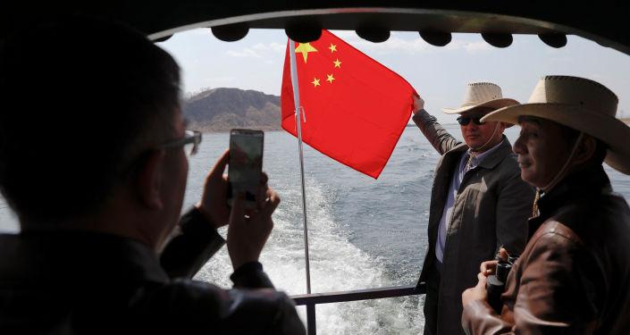 Turisté se fotí s čínskou vlajkou