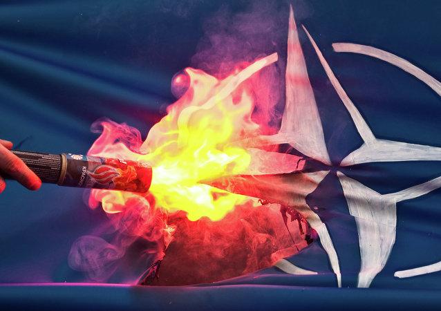 Pálení vlajky NATO demonstrantem