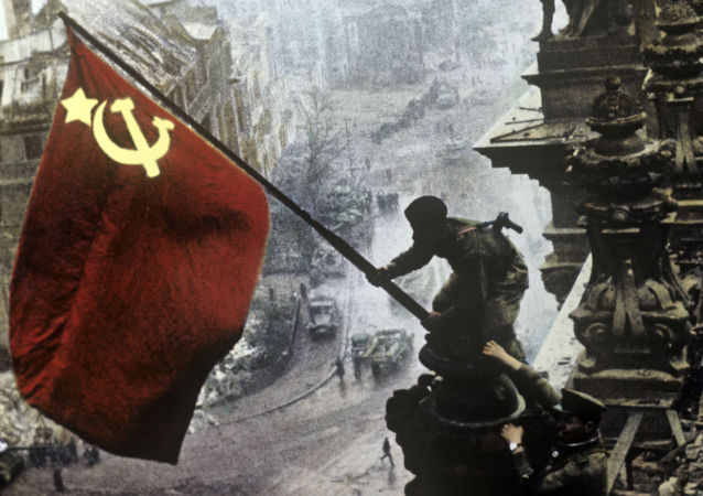 Sovětský voják vztyčuje rudou vlajku nad Reichstagem