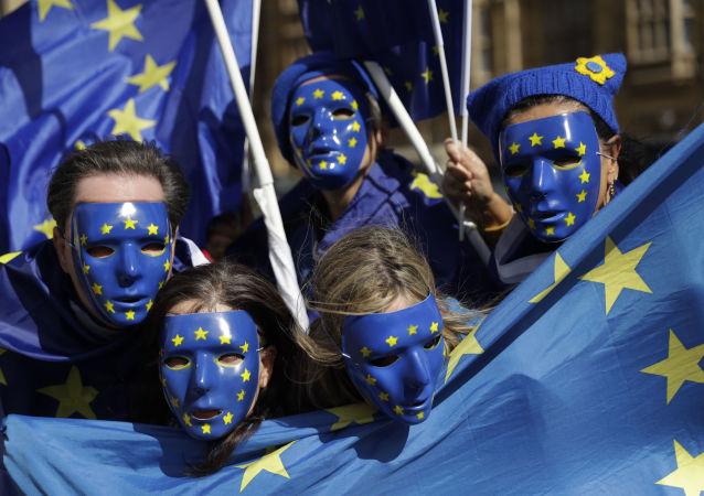 Mladí lidé s vlajkami EU